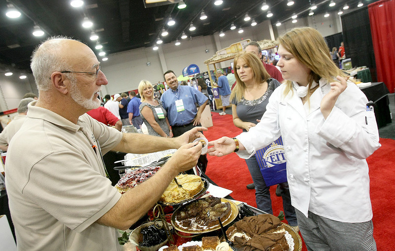 Steve Long with Kelley Brokerage Inc. gives out dessert samples to Allison Cameron and Tami Balzanna at the 2011 Oklahoma Restaurant Convention & Expo at the Cox Center Wednesday. PHOTO BY MAIKE SABOLICH