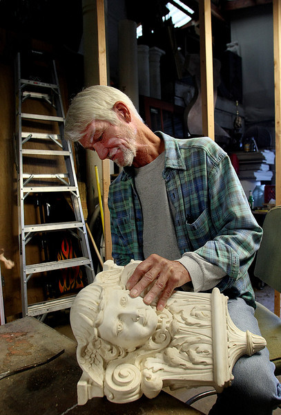 David Schlemme of Akanthos works on the details of a molded stone figure in his Tulsa shop.