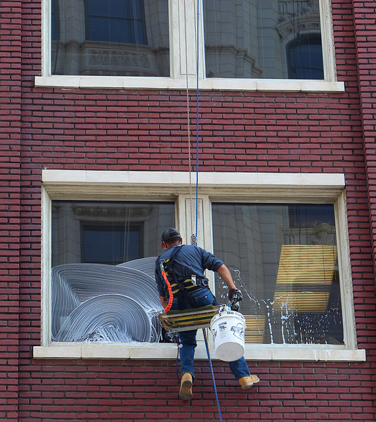 A window washer works his way down the side of the Kennedy Building in a bosons chair in downtown Tulsa.