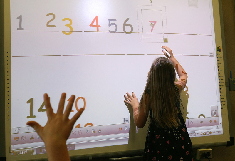 Addyson Day in Mrs Venk's Kindergarten class at Truman Primary School in Norman, orders numbers on the class's interactive white board Friday. PHOTO BY MAIKE SABOLICH