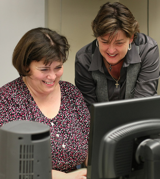 Director of Health Information Technology for TCC Sandy Smith and Adjunct Professor Charlotte Stith work on electronic medical records software in a downtown Tulsa TCC classroom.