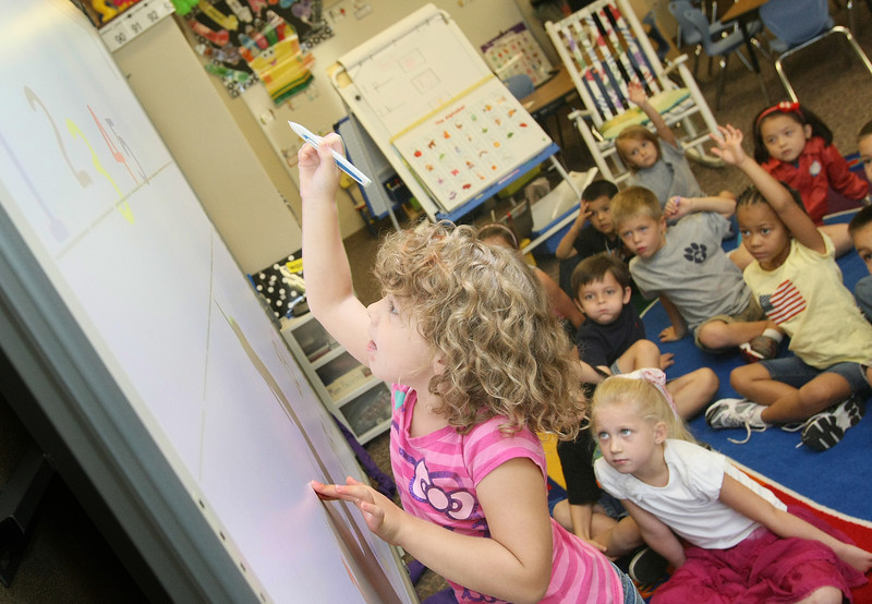 Alyson Wessler in Mrs Venk's Kindergarten class at Truman Primary School in Norman, orders numbers on the class's interactive white board Friday. PHOTO BY MAIKE SABOLICH