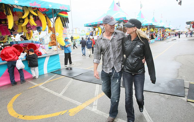 A couple walks across the fairgrounds during the Oklahoma State Fair opening day Thursday. PHOTO BY MAIKE SABOLICH