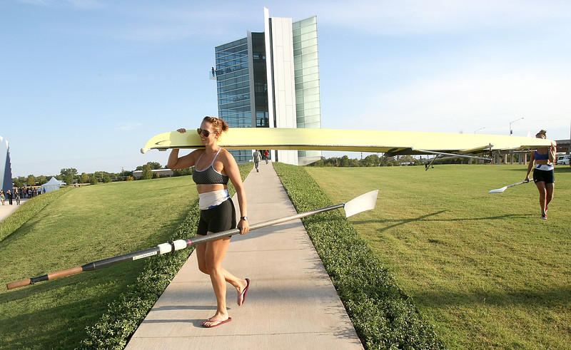 Megan Smith and Meg George carry a rowing boat in front of the new Chesapeake Finish Line Tower Wednesday. PHOTO BY MAIKE SABOLICH