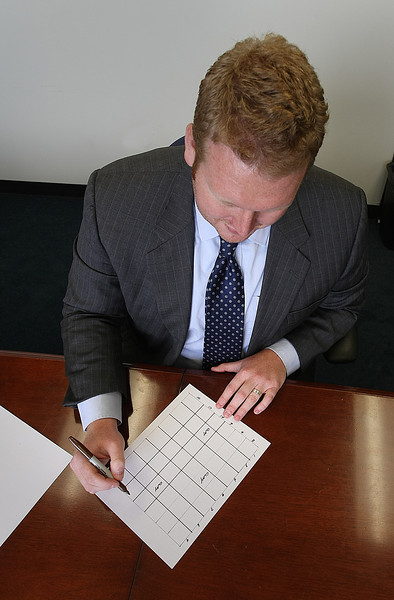 Clay Landrum at Robert Half in Tulsa lays out a grid typically used in office pool.