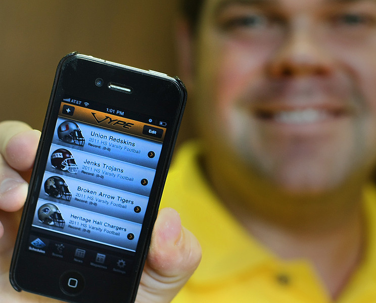 Austin Chadwick, Editor in Chief of Vype Magazines in Oklahoma, holds the company's new IPhone app which allows users to check on every high school game in the state.