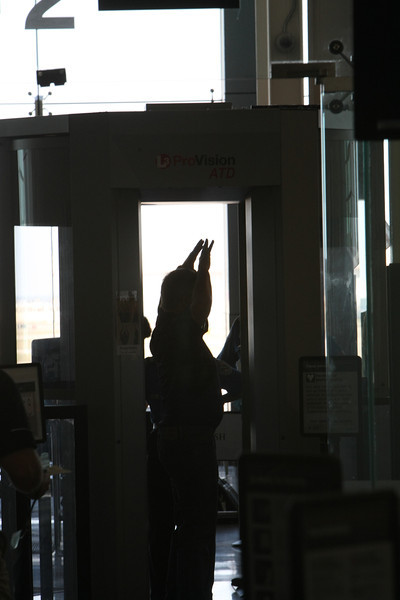 A passenger at the Tulsa International Airport holds his hands above his head as he passes through a security screener before being allowed to board his flight.