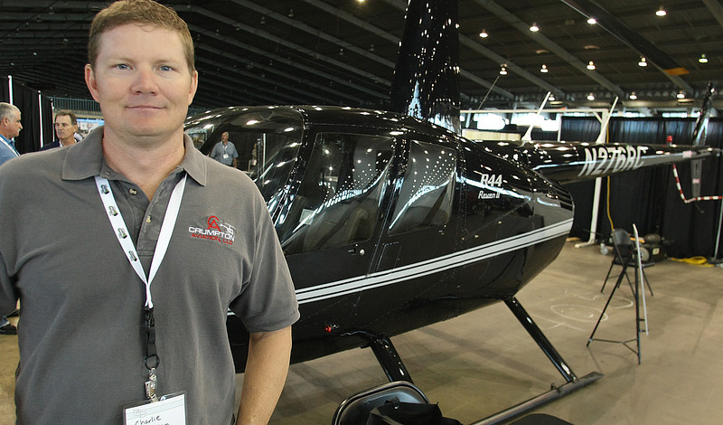 Pilot Charlie Crumpton stands next to the R44 helicopter his company flies.