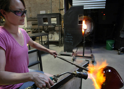 Rachel Haynes heats up a bowl she is working on at the at the Tulsa Glassblowing Studio.