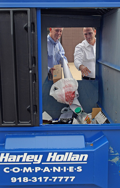 Small business owners Tim Airhart and Mike Morris load  their companies trash into a Harey Hollan dumpster.  Harley Hollan recycles nearly 90% of all refuse.