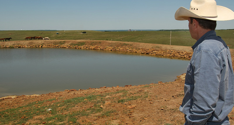 Robert S Hughes II stands next to a stock pond constructed by the OERB  to replace a large salt flat created by past oil drilling on his ranch.