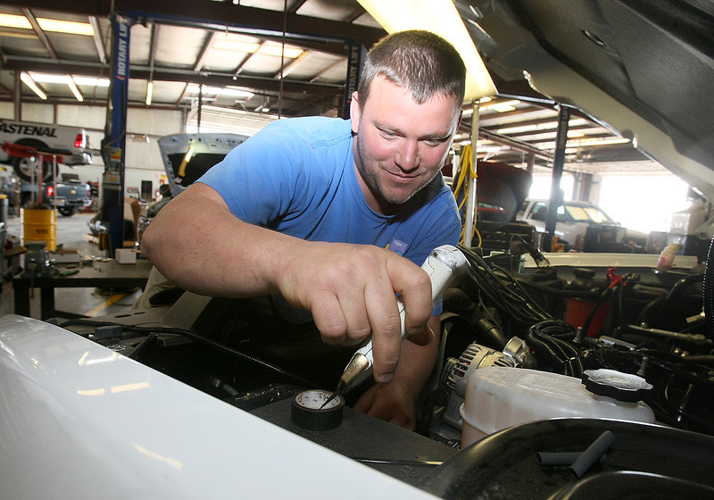 Hunter Robinson install a conversion kit in a vehicle at OEM Systems in Okarche Friday. PHOTO BY MAIKE SABOLICH