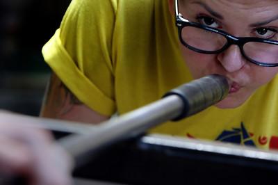 Natalie Keener helps Rachel Haynes work on a bowl at the Tulsa Glassblowing Studio.