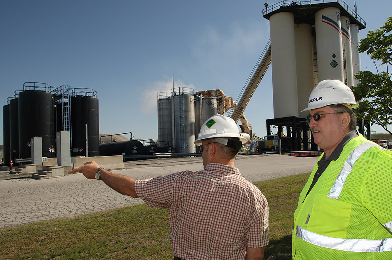 Larry Patric (R), Executive Director Oklahoma Asphalt Pavement Association, chat with Heath Waddel at the APAC plant in East Tulsa.