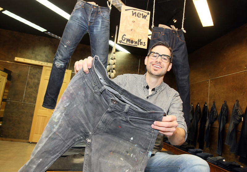 Caleb arter, owner of Blue 7, with jeans that are part of the store's exhibit.  PHOTO BY MAIKE SABOLICH