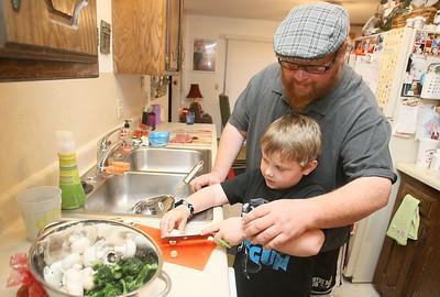 John Biebrich and his son Sean work on cutting mushrooms for a stir fry. PHOTO BY MAIKE SABOLICH