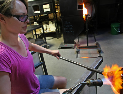 Rachel Haynes works to heat up a bowl she is working on at the at the Tulsa Glassblowing Studio.