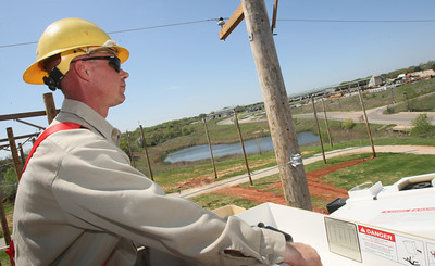 Mark Wagner, journeyman lineman with Edmond Electric on a bucket truck in Edmond Monday. PHOTO BY MAIKE SABOLICH