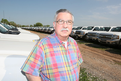 John Luber, general manager of Carter Chevrolet and director of CNG Strategies, in front of a flett of vehicles that still need to be converted to natural gas in Okarche Friday. PHOTO BY MAIKE SABOLICH