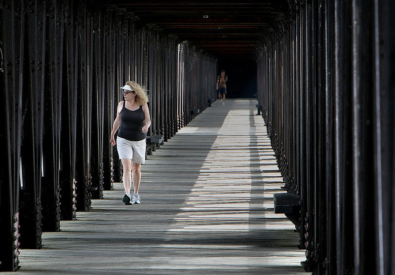 Mary McGraw crosses the Zink dam bridge during her morning walk.