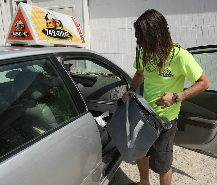 Zandy Crawford, driver for 742-DINE, loads his car to deliver lunch in Tulsa.