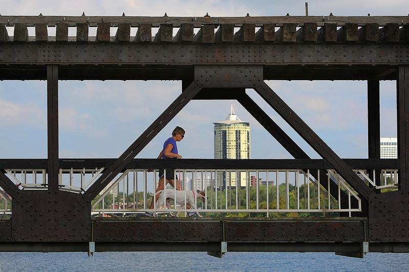A women crosses the Zink Dam bridge while taking her dog on a morning walk.  The iconic University Club Tower can be seen in the background.