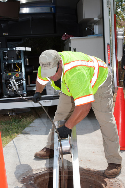 Jeff Everett, retracts a tether from a remote camera sent into the drainage system to look for masquitos., with Oklahoma City public works