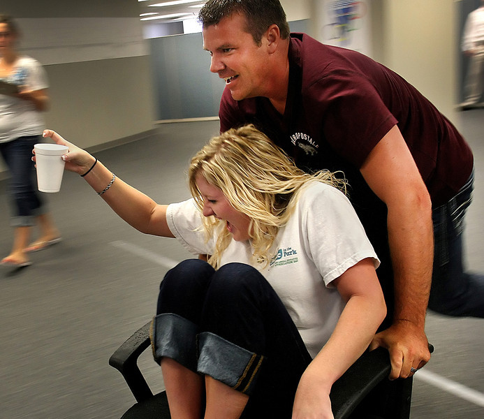 Amanda Gamble laughs as David Ayres pusher her in an office chair during the conclusion of CFS Two's Office Olympics competition. The team had to negotiate and obstacle course without spilling water from the cup Gamble held.