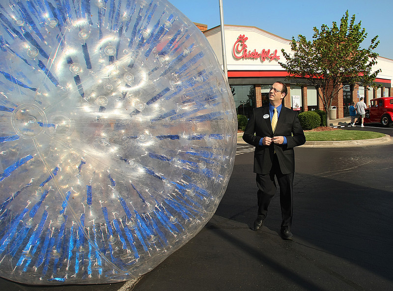 Arthur Greeno, Owner of a Tulsa Chick Fil-A restaurant, inspects one of the 20 hamster balls he is using in relay race to raise money for charity.