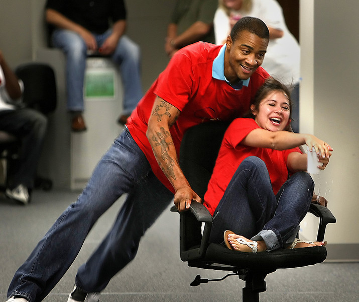 Andrea Anderson laughs as Chris Linder pusher her in an office chair during the conclusion of CFS Two's Office Olympics competition. The team had to negotiate and obstacle course without spilling water from the cup Anderson held.