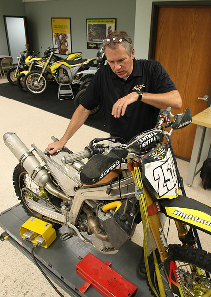 John Fitzpatrick, President and CEO of Highland Inc, examines a motorcycles at the companies Tulsa Office.