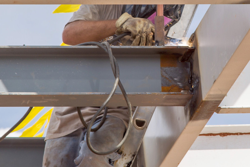 A welder works on the roof of a new pavilion that will be located on the Northeast corner of Chesapeak.