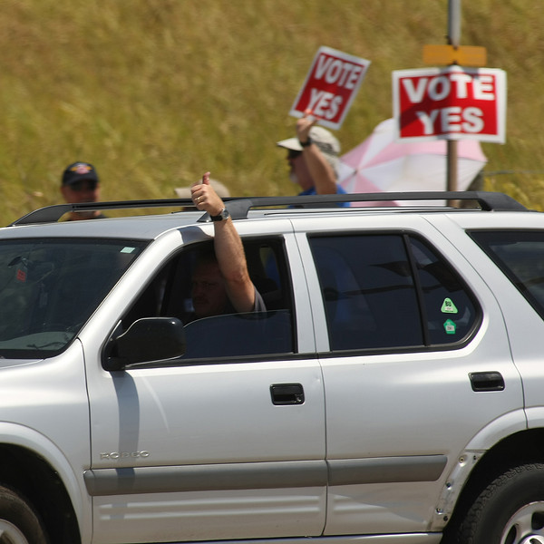 A passing motorist gives picketers the thumbs up as he turns into work at American Airlines.