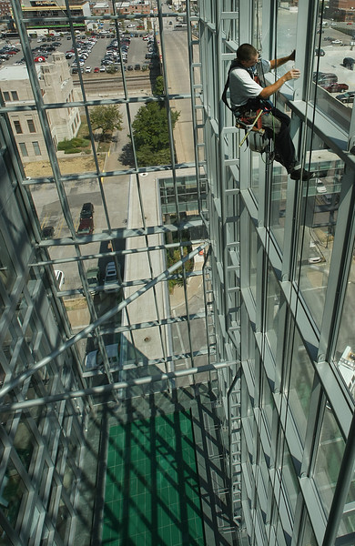 Suspended on a bosun's chair Tony Meek of Landers Window washers cleans the interior windows at the City Hall in Tulsa.