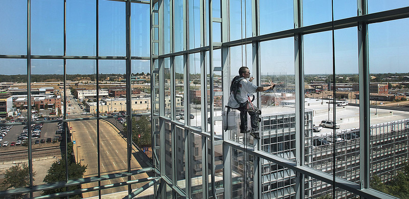 Suspended on a bosun's chair Tony Meek of Landers Window washers cleans the interior windows at the City Hall in Tulsa.  The Brady Art District can be seen in the background on the left side of the picture.