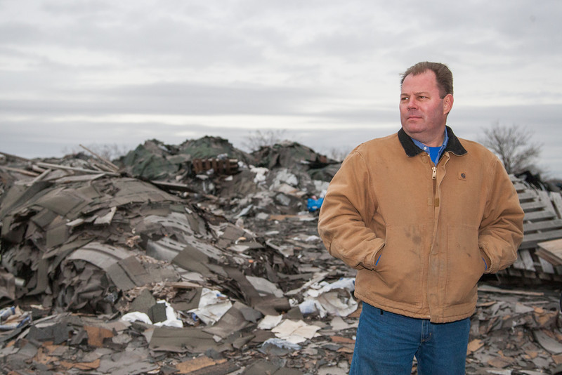 Tony Parker stands atop a 50-foot high mountain of shingles, construction and demolition waste and other unknown debris. He bought the property after the state Department of Environmental Quality determined the site was a safety and environmental hazard. Parker is working with the agency to clean up the mess; he hopes to separate out the shingles and recycle them into asphalt material for state highways. Photo by Brent Fuchs.