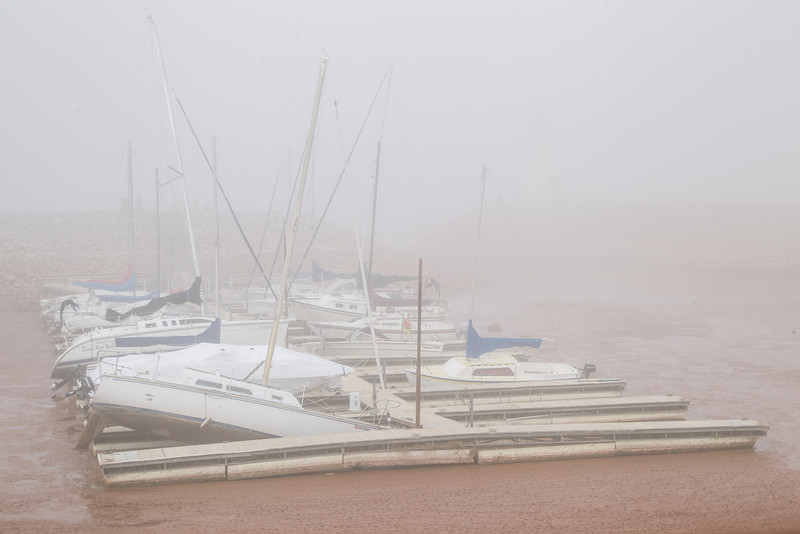 Seen through the fog boats at a dock sit in mud while the water level remains low following this summers draught. Lake Hefner does not reley on rain water to keep the water level up but the water sources used to fill the lake do.