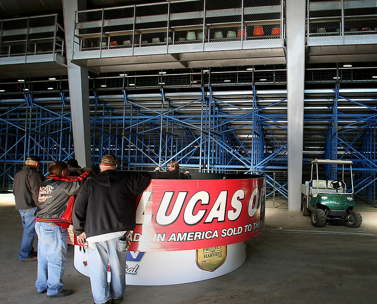 Workmen assemble a sign that will hang over the Chili Bowl nationals at the Tulsa fairgrounds.