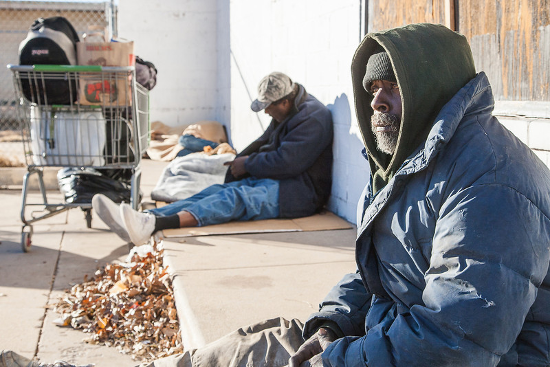 Three homeless men keep warm in an empty parking lot.