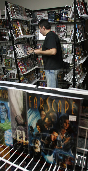 Jimmy Jarman, owner Wizard's Asylum Comics and Games in south Tulsa, restocks shelves on the day after Christmas.