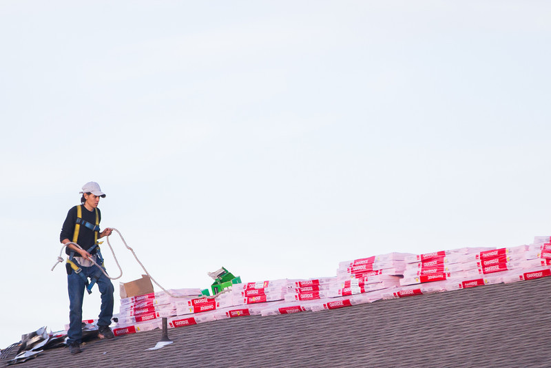 Workers re-roofing an apartment complex in northern Oklahoma City.