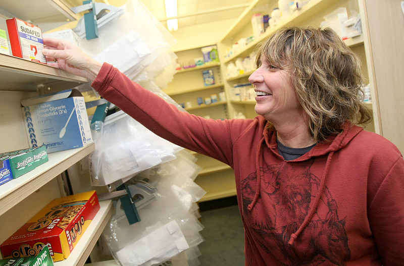 Julie McKellips, pharmacy Tech at Don Cody Pharmacy, places sudafed on the shelves THursday. PHOTO BY MAIKE SABOLICH