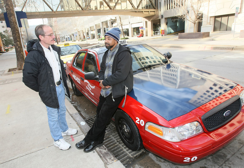 Cab drivers David Pinson and Greg Dotson hang out downtown waiting for clients Tuesday on the corner of Main and Broadway. PHOTO BY MAIKE SABOLICH