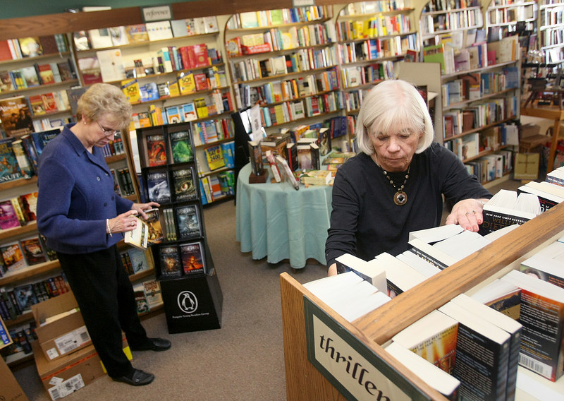 Kathy Kinasewitz, right, and Julie Hovis, co-owners of Best of Books in Edmond, organize books in their book shelves Tuesday. PHOTO BY MAIKE SABOLICH