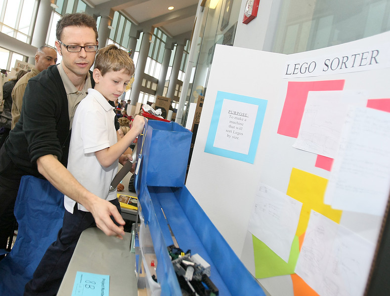 Bryan Green helps his son Ewan Green with his Lego sorter at the Invention Convention at Rose State College Tuesday. PHOTO BY MAIKE SABOLICH