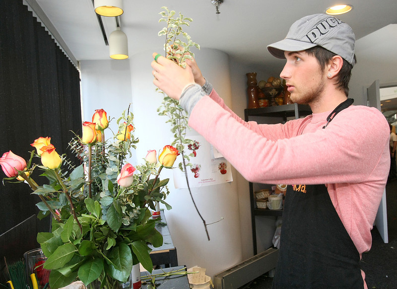 Jared McManus makes a Valentine's bouquet at Floral and Hardy downtown Tuesday. PHOTO BY MAIKE SABOLICH