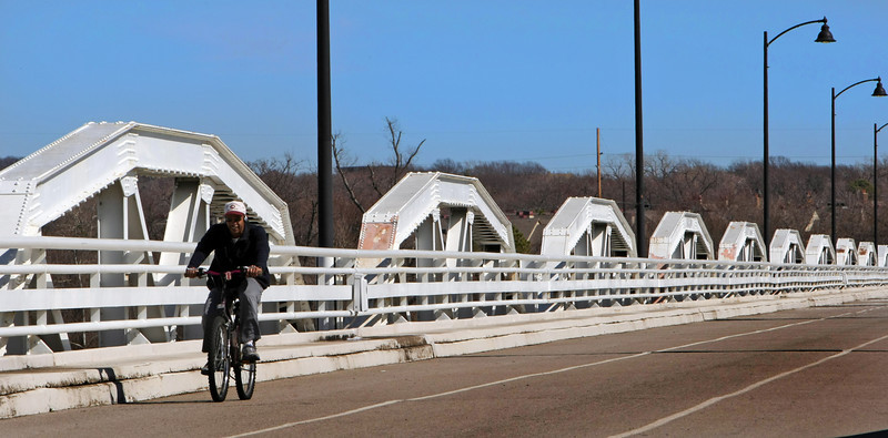 Taking advantage of the unseasonably warm weather a bicyclist rides  across the old Jenks bridge Thursday.