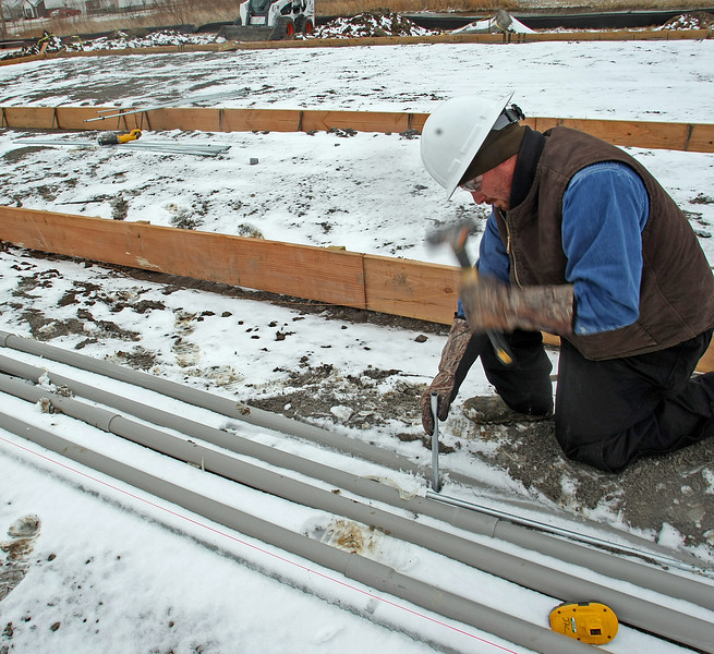 Jerred Crawford stakes out electric conduit at the construction on Phase 4 of the Greens Apartments complex in Owasso.
