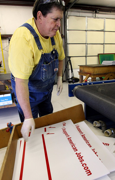 David Walls, American Airline mechanic, helps print yard signs designed to help raise awareness of the employees struggles as the company goes through bankruptcy.