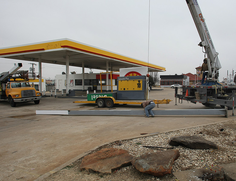 Workmen remove signage from former convenience store at 2109 S. Sheridan in Tulsa.  Kum & Go, L.C. has purchased a 1.17 acre  site was purchased from for $665,000.00 and plans to raze the existing building  and build a new store on the site.